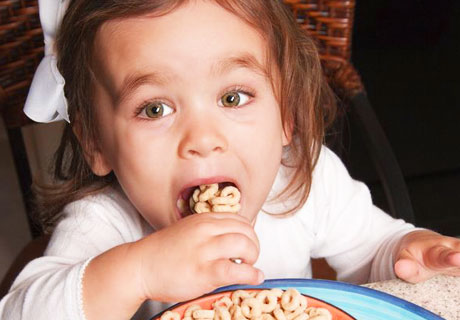 Young girl eating cereal.